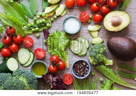 Overhead view of ingredients for salad, fresh tomatoes, cucumber, avocado, lettuce, spring onion, broccoli on the grey wooden table, selective focus
