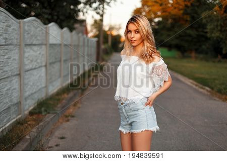 Beautiful Woman In Vintage T-shirt With Denim Shorts Outside The City On A Summer Day