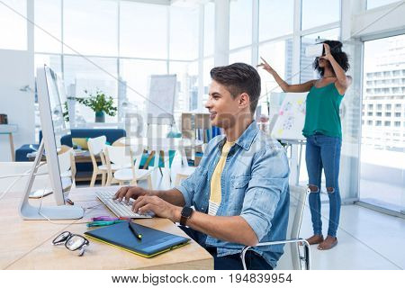 Male executive working on computer while female executive using virtual reality headset in the office