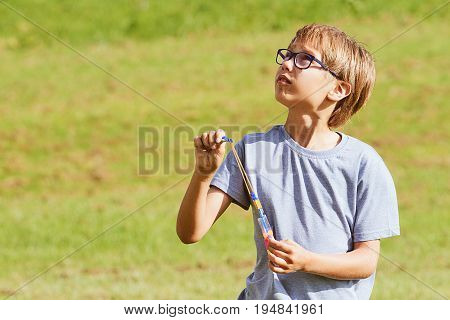 Boy playing outdoors in a park with arrow helicopter elastic rocket toy