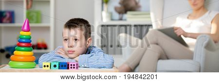 Child looking at colorful toy pyramid during a therapy session