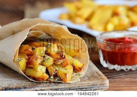 Crunchy fried potatoes with spices. Spicy fried potatoes in paper, ketchup sauce. A wooden background. Quick potato recipe. Closeup