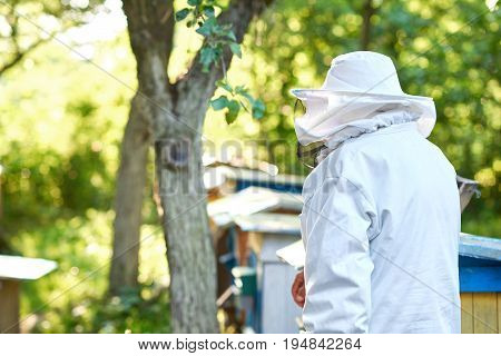 Rearview shot of a beekeeper in a suit standing in the garden copyspace.