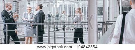 Group of investors negotiating contract talking in modern interior panorama