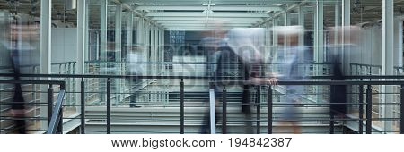Blurred image of busy business people in industrial interior panorama