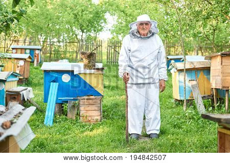 Shot of a professional senior male beekeeper wearing beekeeping suit standing in the garden of his apiary copyspace.