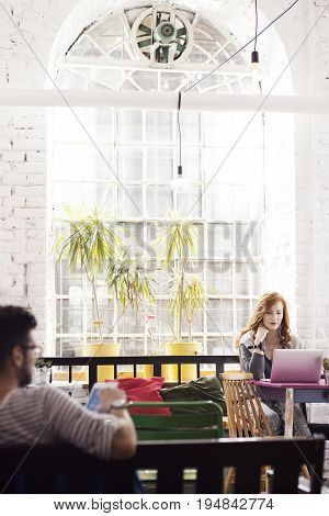 Woman working as freelancer in bright industrial interior with big window