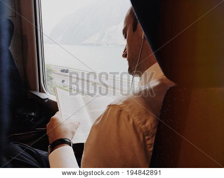 Milan Italy - June 13 2017: male businessman passenger train is reading a book