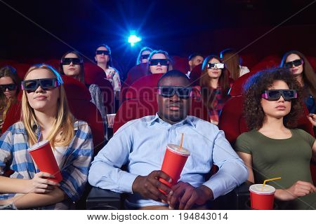 Young people wearing 3D glasses watching a movie at the local cinema technology recreation diversity youth weekend activity concept.