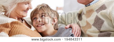 Smiling grandma sitting on a sofa and hugging her happy grandson