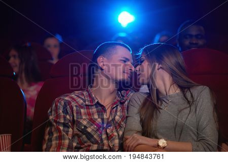 Low angle shot of a young loving couple sharing romantic moment on a date at the cinema touching noses love romance affection couples relationships dating entertainment leisure.