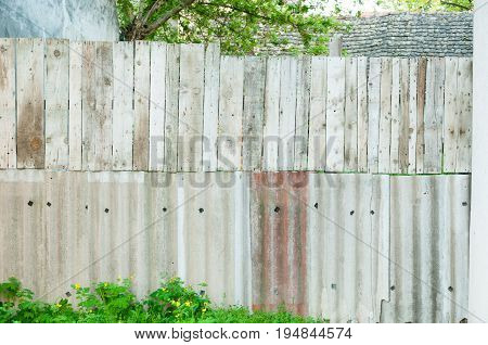 Improvised fence of wooden planks ceramic tiles for the roof. Handmade fence.