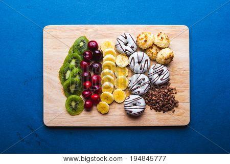 plato de dulces y frutas sobre una tabla de madera