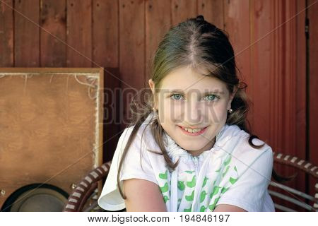 Outdoor portrait of a teenage girl with a shy look in her face wooden wall in he background