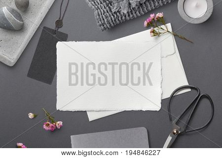 elegant feminine stationery mockup with hand made paper greeting card, pink flowers and lifestyle objects on a grey paper background, flat lay / top view styled photography