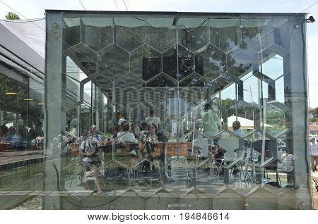 GAIA, PORTUGAL - AUGUST 7, 2015: Outdoors reflections on crystal facade and people inside it of modern restaurant in Gaia Portugal.