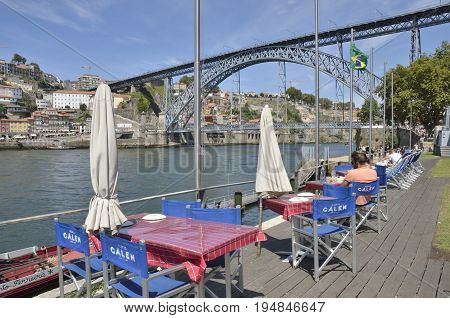 GAIA, PORTUGAL - AUGUST 7, 2015: People at outdoors restaurant in the promenade of Gaia with views to the promenade of Porto in Gaia Portugal.