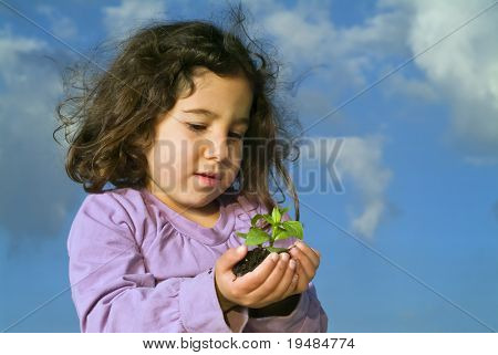 little girl holding plant against blue sky with clouds