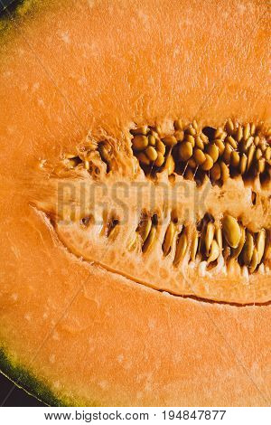 Melon seeds background and texture. Close up view of melon cut in a half with seeds. Organic texture and background. Fresh fruit. Macro view of melon surface. Melon texture. Healthy food.