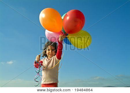 girl holding balloons against blue sky