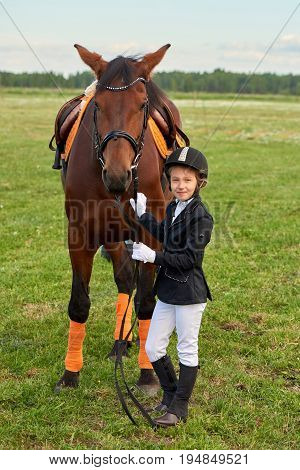 Pretty little girl jockey lead horse by its reins across country in professional outfit