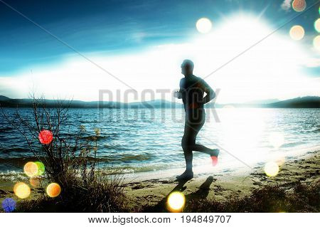 Film Grain. Silhouette Of Tall Sport Active Man Running And Exercising On Beach At Busch Below Sunse