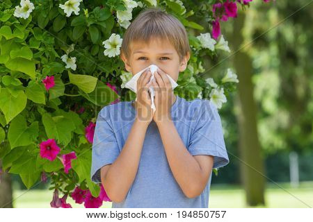 Allergy. Child is blowing his nose near blossoming flowers
