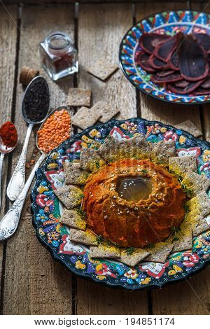 Spicy lentil dip with rusks and spices on arabian plate and wooden background background, top view