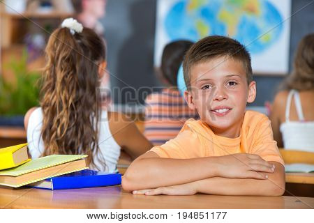 Smiling Boy In Classroom At School