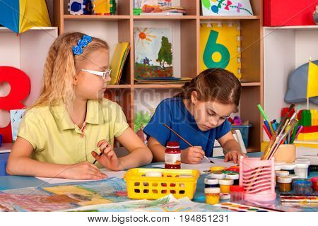 Small students painting in art school class. Child drawing by paints on table. girl in kindergarten. Drawing education develops creative abilities of children. Childish envy in prep school.