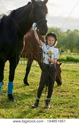 Pretty little girl jockey communicating with her black horse in professional outfit