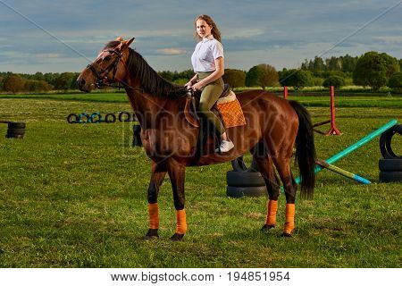 Pretty young girl riding a horse across country