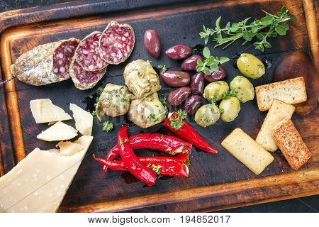 Traditional Italian Antipasti with Salami and Vegetable as top view on old burnt cutting board