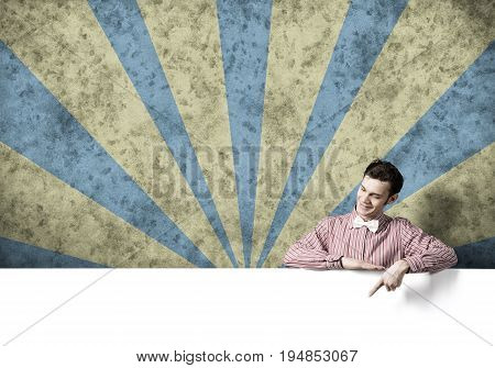 Young funny guy in checked shirt pointing with finger at  blank banner