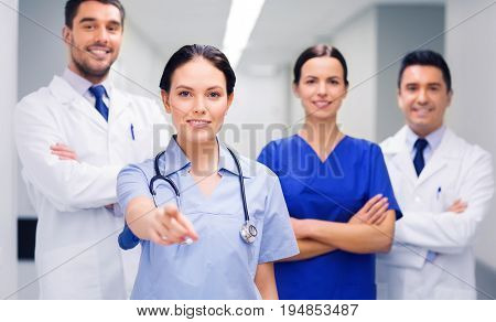 clinic, profession, people, health care and medicine concept - group of happy medics or doctors pointing finger on you at hospital corridor