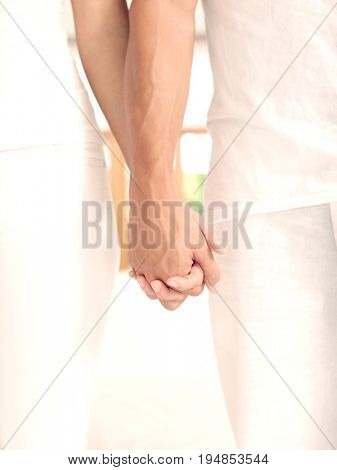 Closeup midsection of an affectionate couple holding hands