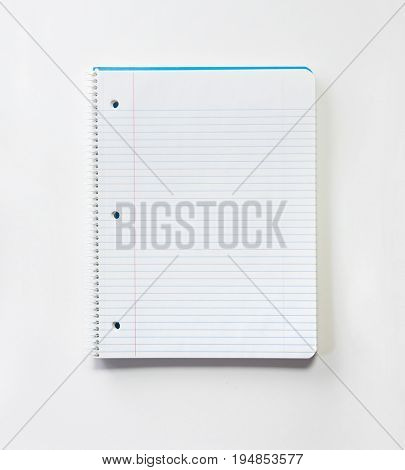 Blank note book with three ring binder holes and red margin line, isolated on natural white.