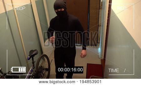 Kursk, Russia, June 30 :the masked robber burst through the door and threatened with a knife in CCTV camera.