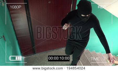 surveillance camera caught the robber in a mask with a knife.