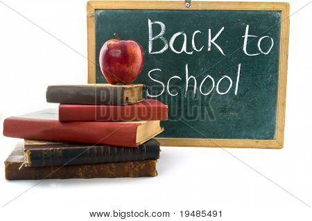 red apple on pile of old retro books in front of an old blackboard