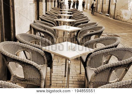 Table and wicker chairs of street cafe in Valladolid, Spain