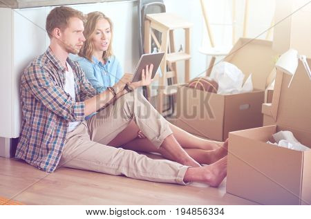 Young couple moving in new home.Sitting and relaxing after unpacking.Looking something on laptop