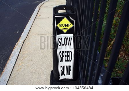 Slow speed bump sign on the road near a fence
