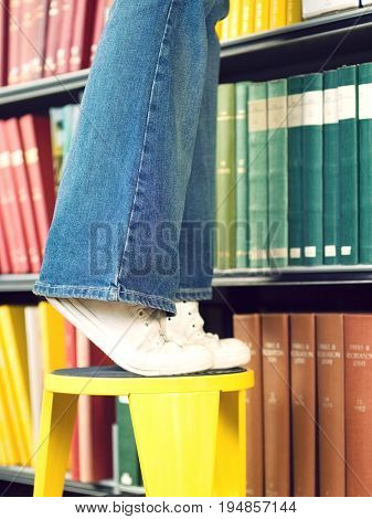 Closeup lowsection of a young man standing on stool reaching for book in library