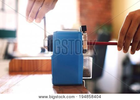 Closeup of woman's hands using blue pencil sharpener at table