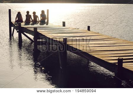 Rear view of young boys and girls sitting on edge of jetty at lake