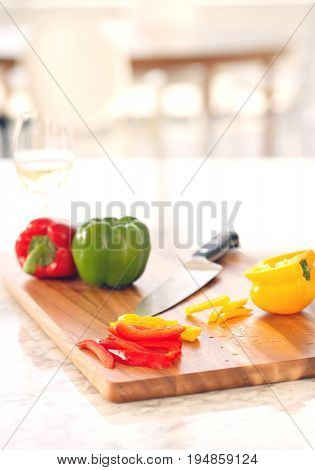 Peppers and knife on chopping board in kitchen