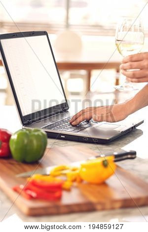Closeup of man's hands with wineglass using laptop next to chopped bellpepper in kitchen