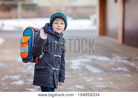 Little school kid boy of elementary class walking to school. Happy child having fun and playing with first snow. Student with backpack in colorful winter clothes. School building
