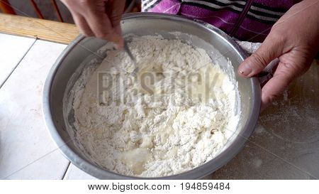 Mixing the dough in a metal bowl. Kneading dough.